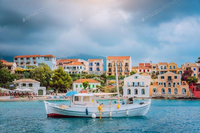 Bahía majestuosa única del pueblo de Assos con barco de pesca en el ancla en frente y nubes en el fondo