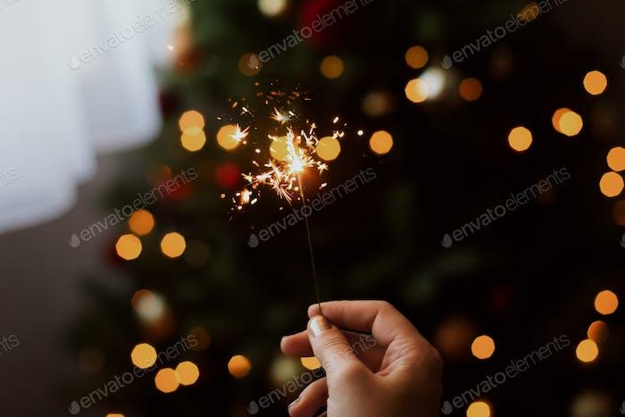 Burning sparkler in hand