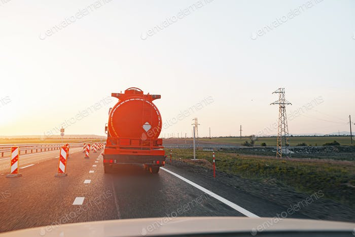 Truck driving on highway road at sunrise