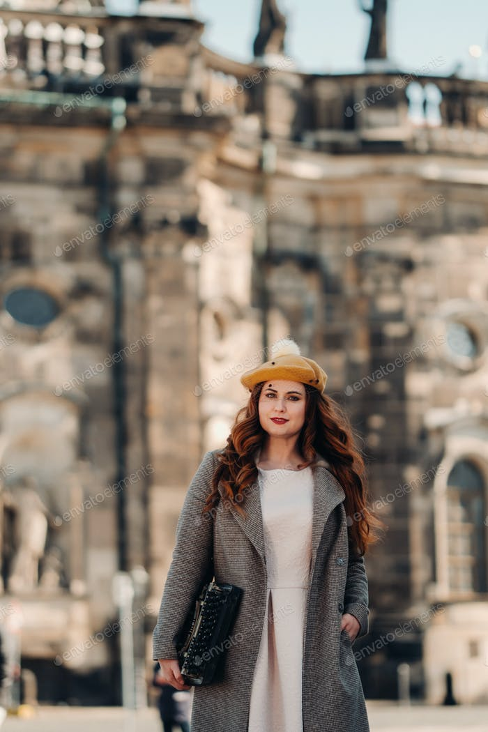 a beautiful girl in a hat stands with a typewriter in the Old city of Dresden.Germany