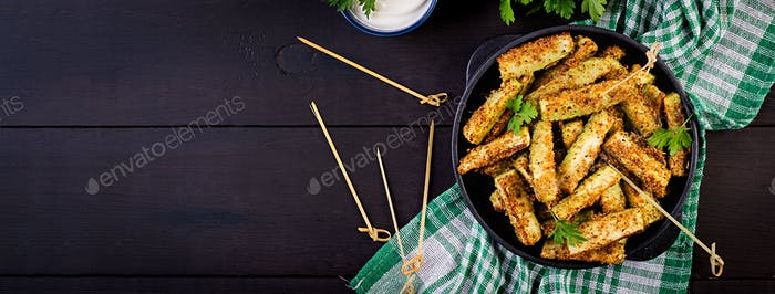 Baked zucchini sticks with cheese and bread crumbs. Vegan food. Vegetarian cuisine. Banner. Top view
