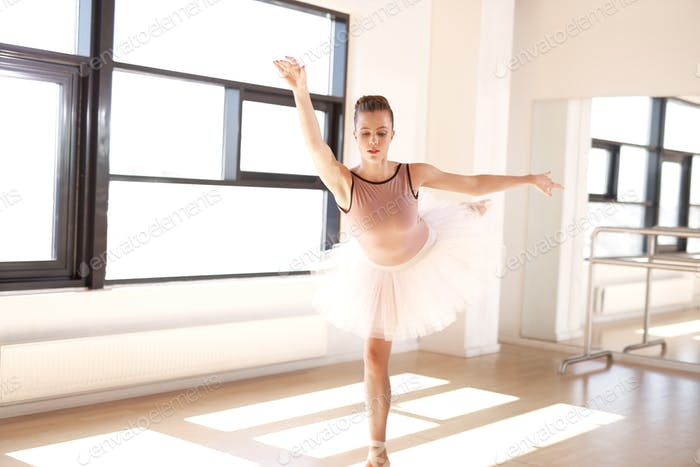 Ballerina in Arabesque Position in Dance Studio