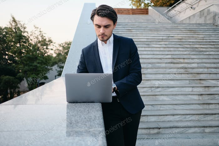 Young handsome man in classic suit standing on stairs outdoors and thoughtfully working on laptop