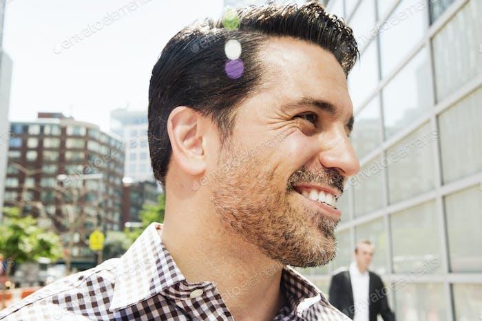 Porträt eines lächelnden Mannes mit braunen Haaren und Stoppeln, trägt ein kariertes Hemd.