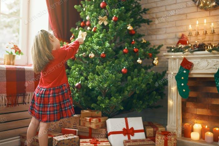 Mädchen schmückt Weihnachtsbaum