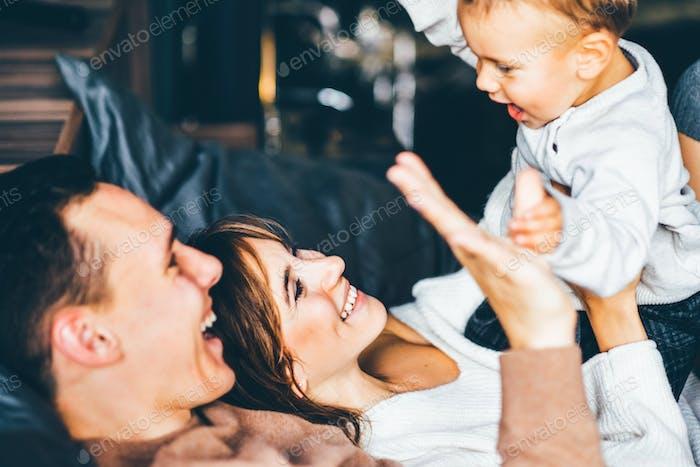 Pais jovens e bebê fofo deitado juntos. Jovens pais abraçados e sorriem.