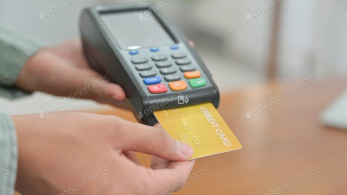 Close - up shot of Employees accept credit card payments via EDC.
