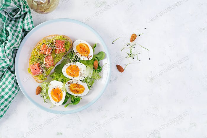 Healthy open sandwich on  toast with avocado and salmon, boiled eggs