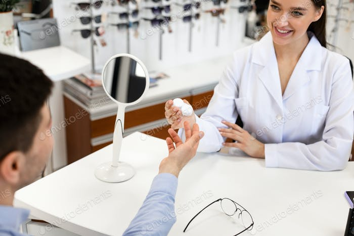 Optician giving plastic case with contact lenses to patient