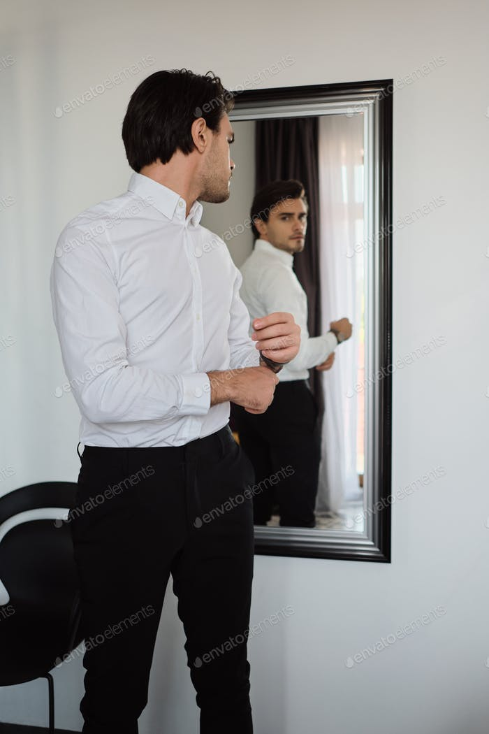 Young handsome man in white shirt and black trousers dreamily looking in mirror at modern home