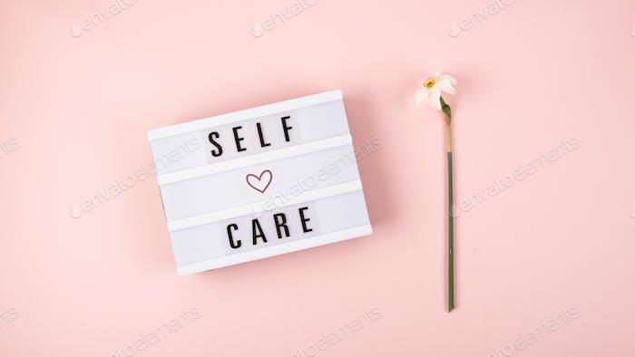 Self-Care-Wort auf Leuchtkasten und Blumen-Narzissen auf rosa Hintergrund flach lag. Kümmere dich um dich selbst