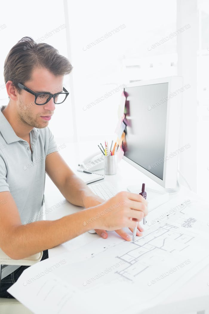 Side view of a concentrated young man using compass on design