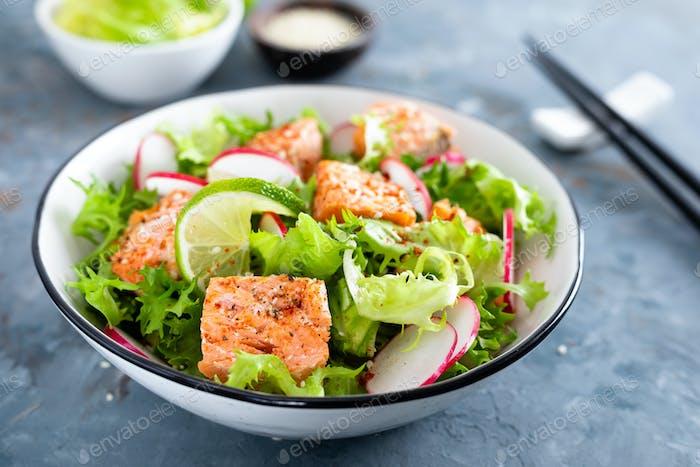 Gesunder Mittagssalat mit gebackenem Lachsfisch, frischem Rettich, Salat und Limette