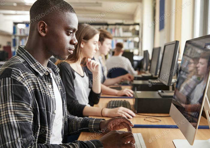 Group Of Students Using Computers In College Library