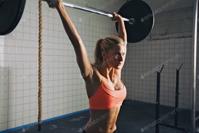 Woman doing crossfit barbell lifting
