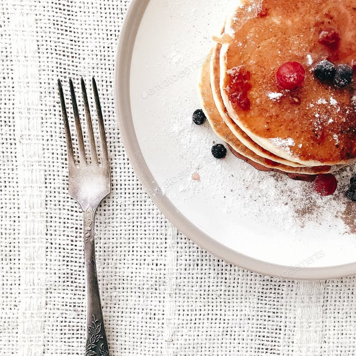Delicious pancakes with syrup and berries on stylish plate