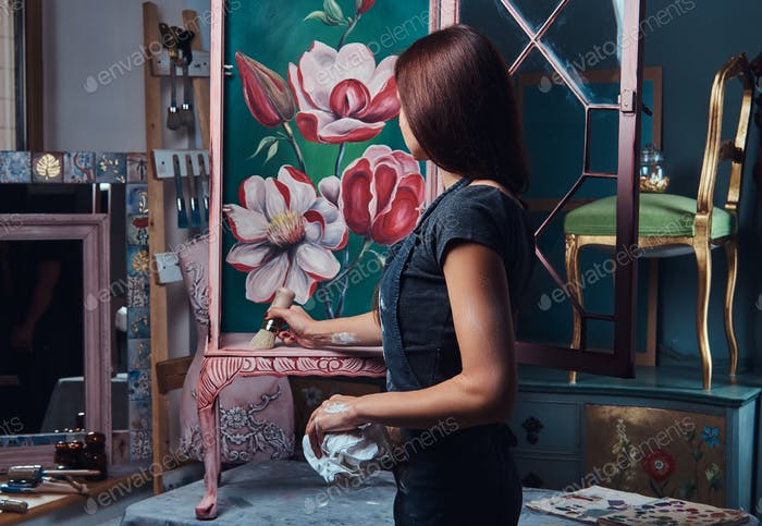 Женщина-художница рисует винтажную книжную полку в мастерской.