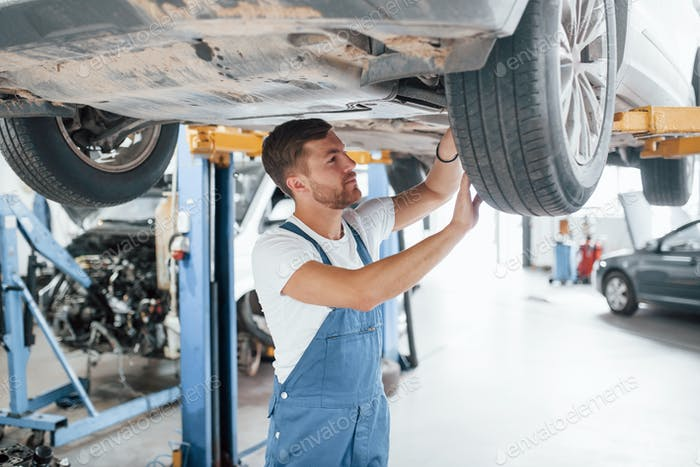 Caucasian ethnicity. Employee in the blue colored uniform works in the automobile salon