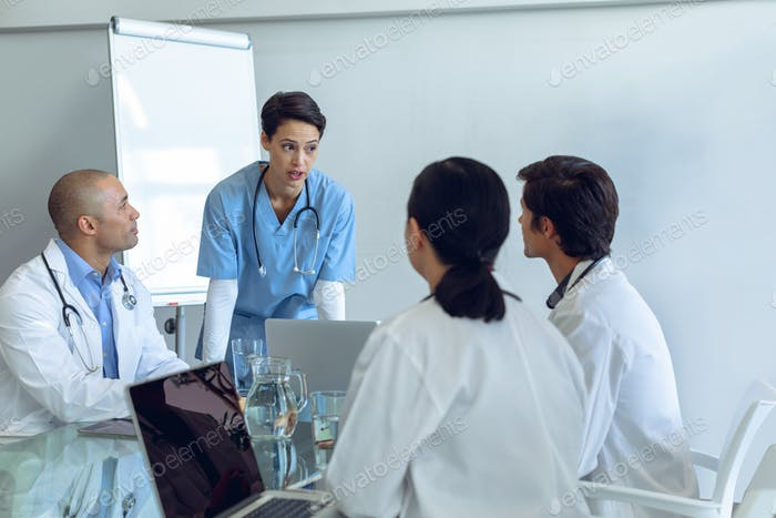 Standing female Caucasian nurse talking to attentive diverse medical team sitting at the table