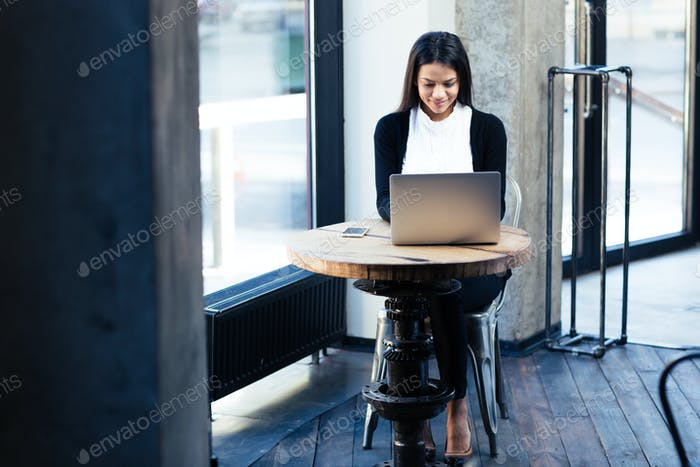 Happy businesswoman using laptop in cafe