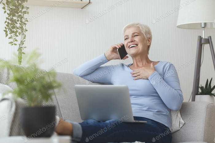 Joyful elderly business lady talking by smartphone
