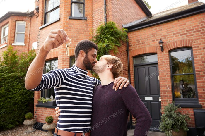 Gay Male Couple Standing Outside New Home On Moving Day Together Kissing And Holding Keys