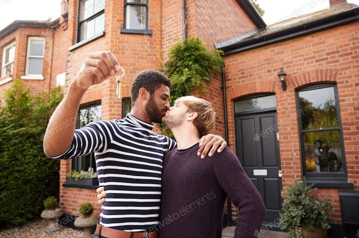 Gay männlich paar stehend außerhalb neue Zuhause auf Umzug Tag zusammen küssen und halten Schlüssel
