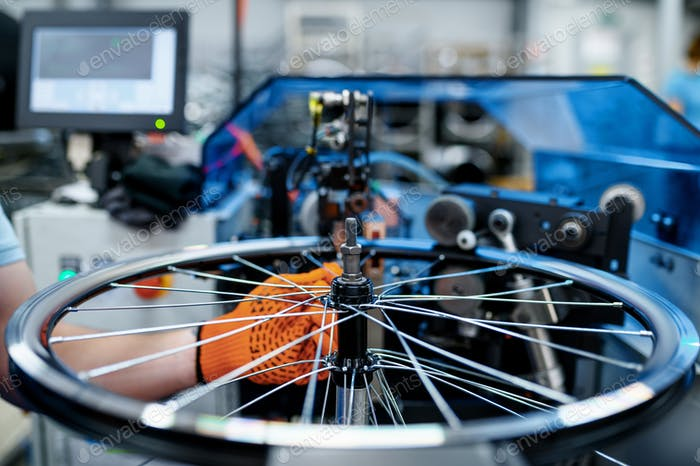 Worker checks bicycle rim on backlash, factory