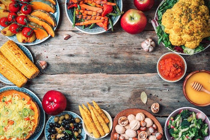 Comida y platos veganos. Calabaza al horno, ensalada, maíz, nueces, verduras, aceitunas, frutas en madera