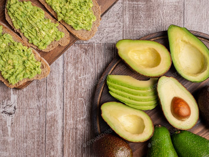 Sandwiches made with avocado on a wooden board