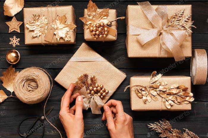 Frau wickelt Weihnachtsgeschenke über Holzhintergrund