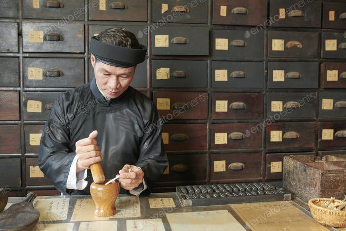 Asian medicine practitioner using mortar and pestle