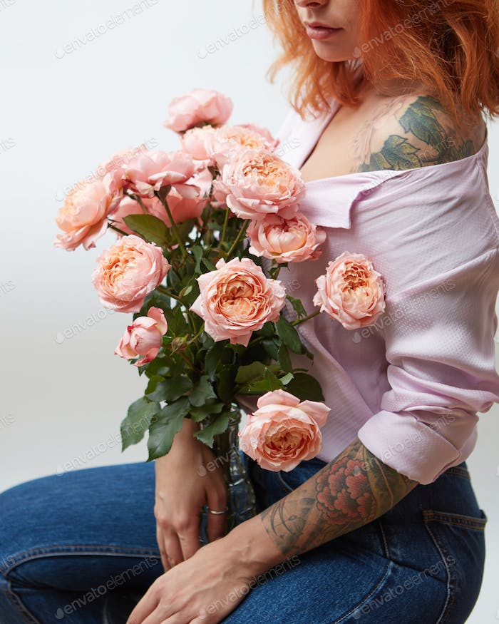 A bouquet of pink roses in a vase holds a girl with a tattoo on a gray background with copy space