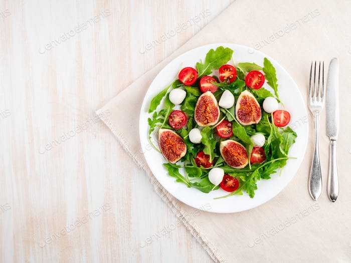 Fresh salad with figs, tomatoes, cucumbers, arugula, mozzarella. Oil with spices,