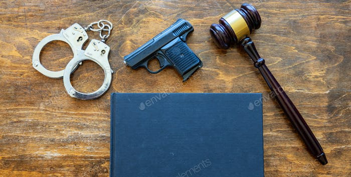 Law, crime, punishment concept. Judge gavel, handgun, handcuffs and a black blank legal book