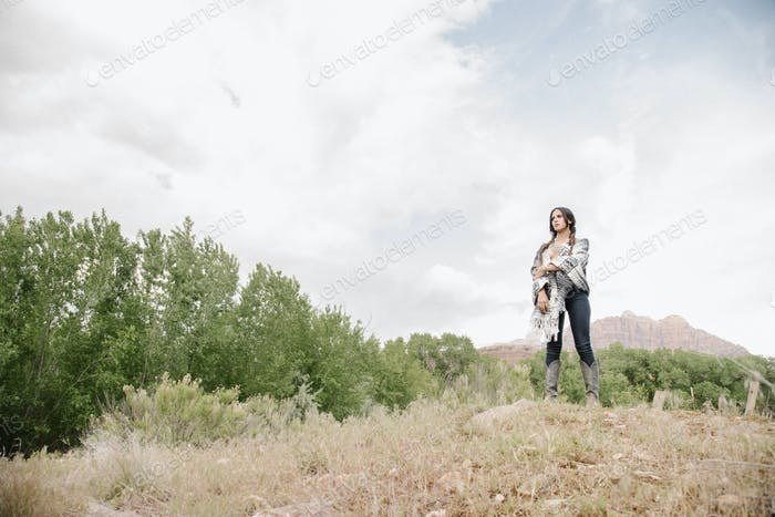 Young woman with long brown hair standing in a prairie under a cloudy sky.
