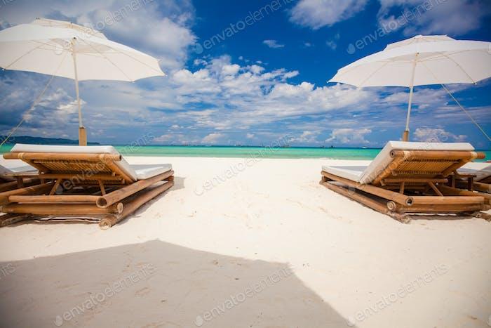 Fantastischer Blick auf tropische leere Sandplage mit Sonnenschirm und Liegestuhl