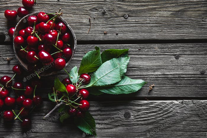 Wooden background with several delicious cherries on green leaves. Wholesome healthy food