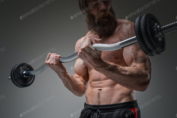 Caucasian handsome athlete looking at barbell he holds it