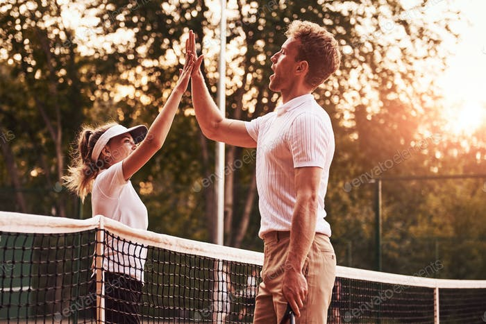 Giving high five. Two people in sport uniform plays tennis together on the court