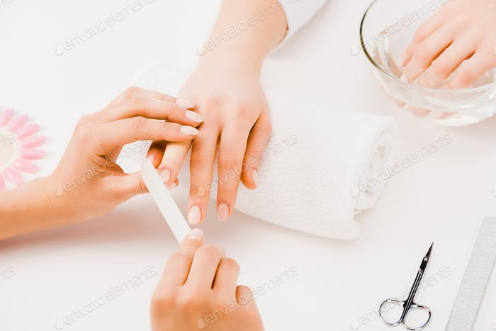Cropped view of manicurist filing nails with nail file