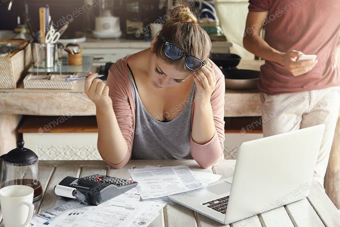 Finanzielle Probleme und Wirtschaftskrise. Indoor-Aufnahme von jungen ungezwungenen Hausfrauen, die Familie finan