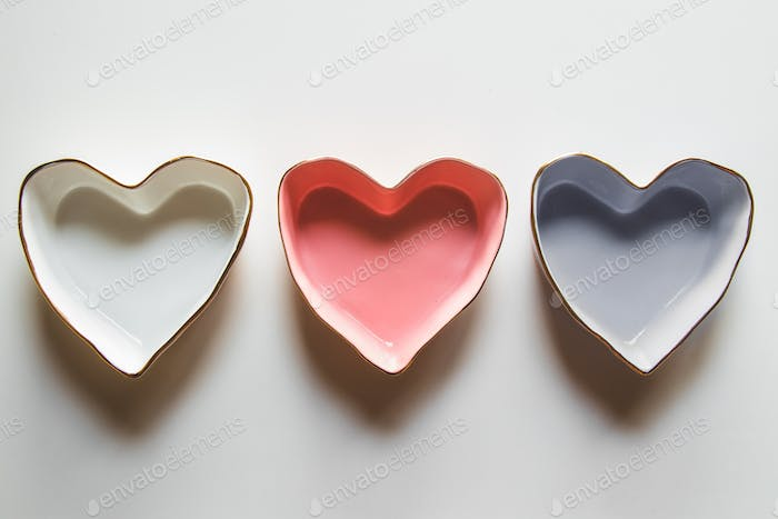 Three plates of hearts on a white background in blue, red and white