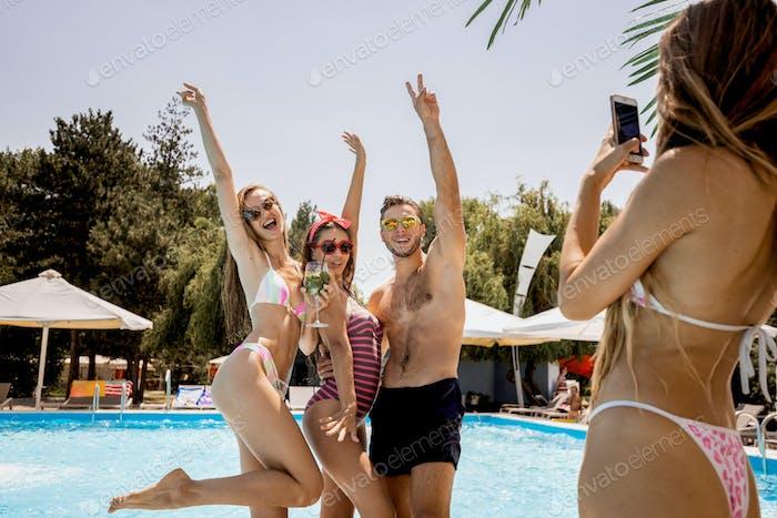 Zwei stilvolle junge Mädchen in den Badeanzügen und Kerl Pose für das Mädchen, das sie neben dem fotografiert