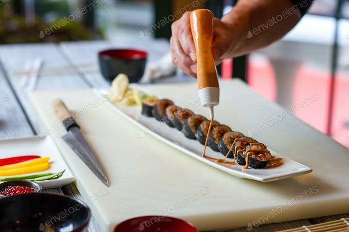 Bottle pours sauce on sushi