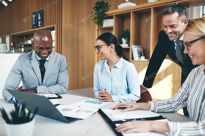 Diverse businesspeople laughing while going over paperwork in a meeting