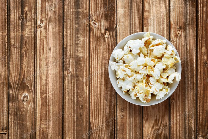 Popcorn in bowl on wooden background