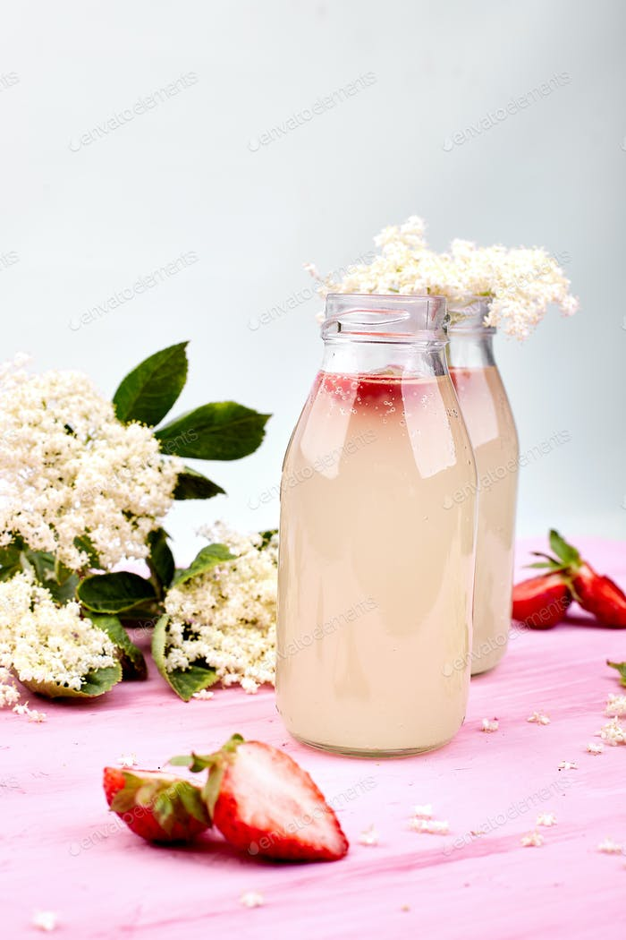 Kombucha tea with elderflower and strawberry on pink background.