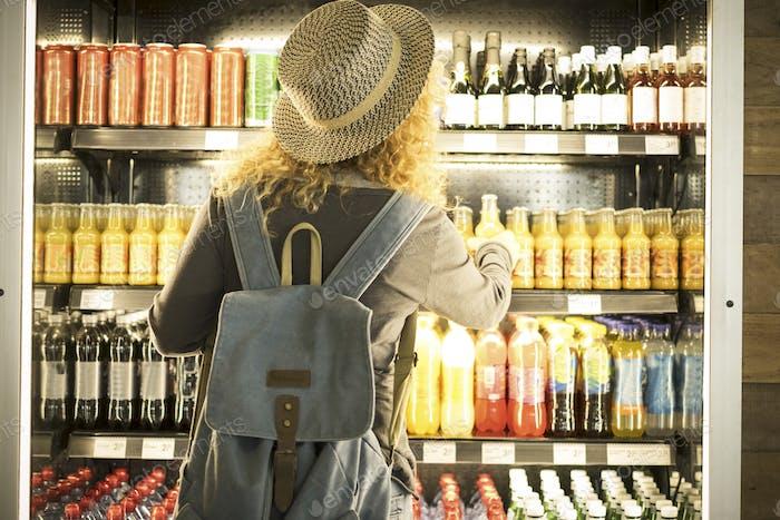 Travel woman viewed from back choosing beverage in a fresh fridge