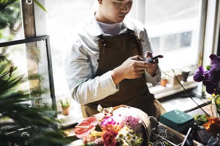 Man sitting using mobile at flower shop